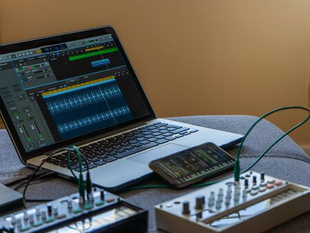 Close up view of fm synthesizer, sampler, smartphone with modular synthesizer and laptop with a DAW. Electronic music concept. Stock Photo