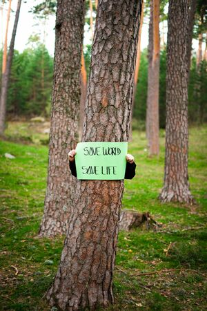 Teenager holding a banner around a tree in the woods. Save world, the life. Vertical image. Concept of sustainability.