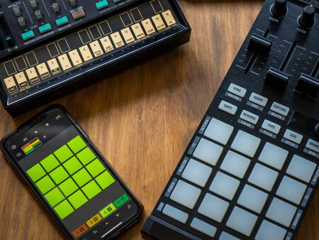 Close up view of fm synthesizer, midi controller and smartphone with drum machine application on a wooden table. Electronic music concept.
