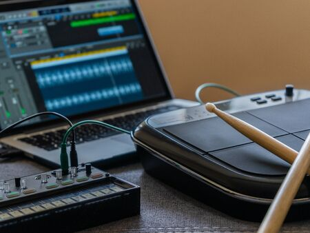 Close up of an electronic battery with drumsticks, an fm synthesizer and a laptop with a music editor. Music concept.