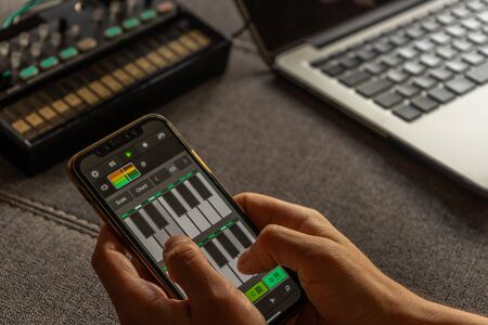 Young boy composing electronic music on his smartphone with a synthesizer application. Electronic music concept.