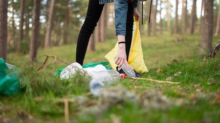 View from the ground of a young girl piking up plastic on the woods. Sustainability concept.