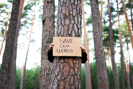 Low view of a teenage activist holding banner around a tree with a environmental message. Save our world. Concept sustainability.