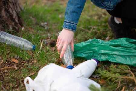 Close up view of a teenage girl hand collecting plastic on the forest. Sustainability concept.