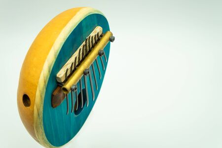 Top view of a blue African kalimba on a white background with space on the right for text. Traditional music concept.