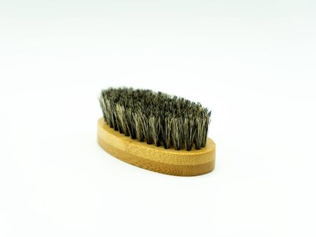 Close up view of a bamboo beard brush with natural bristles on a white background in the center of the image. Facial care concept for men.