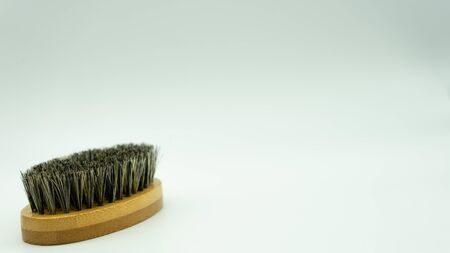 Close-up of bamboo beard brush with natural bristles on white background on the left of the image with space on the right for text. Facial care concept for men.