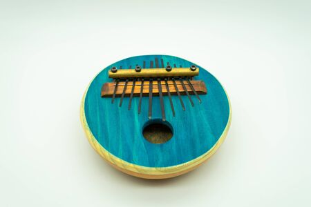 Blue African Kalimba on a white background in the centre of the image. Traditional music concept.