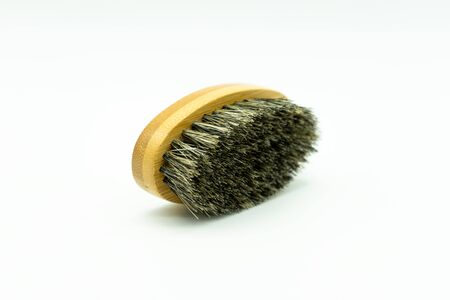 View of a bamboo beard brush with natural bristles lying on a white background Concept of facial care for men. Reklamní fotografie