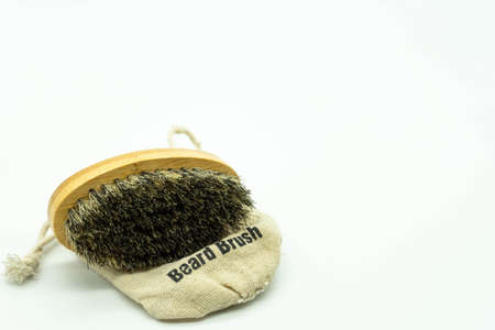 Beard brush with natural bristles, on its case located on the left of the image with white background with space on the right. Concept facial care for men. Imagens