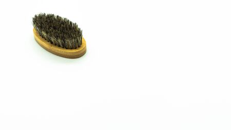 Beard brush made of bamboo on a white background on the left of the image with space on the right. Concept of facial care.