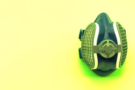 Radioactive green coronavirus mask, isolated on a yellow background with space for text. Concept virus. Covid-19.