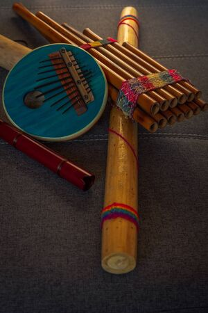 Peruvian instruments handmade in Peru on a sofa. Concept of traditional Andean music. Vertical image.
