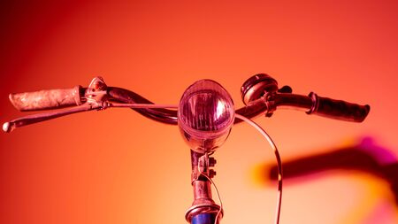 Handlebar with headlight from an old isolated bicycle on a coloured background. Vintage concept. Neon lights.
