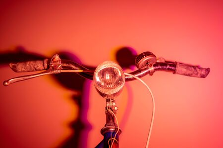 Handlebar with headlight from an old bike with colored shades. Vintage concept. Neon lights.