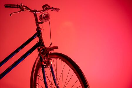 Old bicycle in shadow with isolated front light in colored background. Old bike concept.