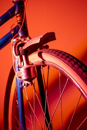 Front wheel of antique bike isolated in colored background. Vintage concept. Neon lights.