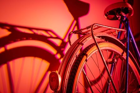 View of the back of an old isolated bicycle on a coloured background. Vintage concept. Neon lights.