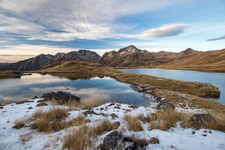 Angelus lakes mirroring fine clouds and blue sky after sunset. Rocky mountains in background with snow, tussock. Angelus mountain hut in the middle
