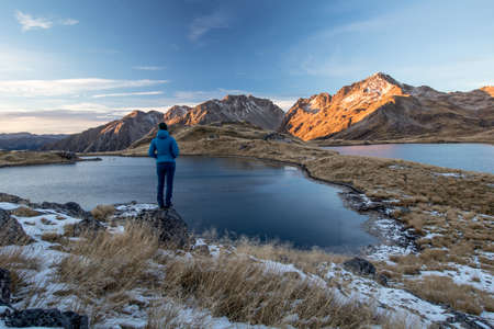 View on Angelus Lakes and winter mountain scene during sunset with sporty young woman standing on a rock facing backwards. Nelson Lakes National Park, New Zealand.