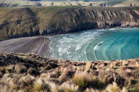 View on periodic waves in rocky Tumbledown bay with black sand beach on Banks Peninsula, New Zealand
