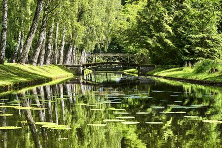 Hermoso puente sobre el canal transversal del jardín del Palacio de Schwerin. Paisaje de agua.