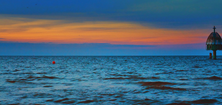 Panorama with dive gondola in the Baltic Sea with colorful sunset in the background. Standard-Bild - 114121005