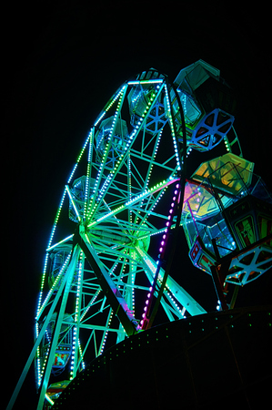 Ferris wheel at night with green light.