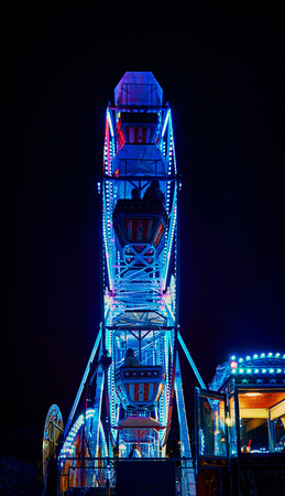 Ferris wheel at night with blue light.