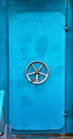 A light blue old ship door on the Baltic Sea.