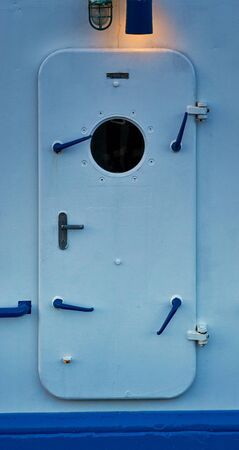 Waterproof door with lamp on a ship. Emergency door.
