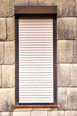 Alte Asbestschindeln mit Fenster und Rollo.