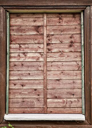 Very old window with wooden shutters. Untidy primitive window.