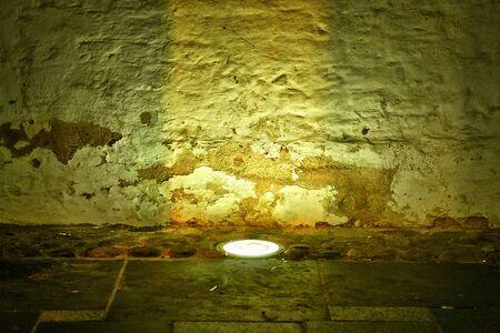 Floor lamp shines on an old broken wall of stone. Standard-Bild - 129479910
