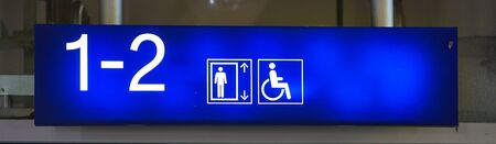 Neon sign with wheelchair symbol in the direction of the elevator at a train station. Stockfoto