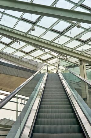 Escalator under a large glass roof.