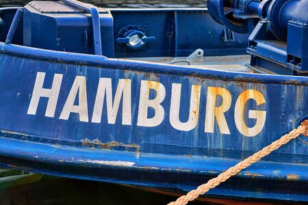 Hamburg in white capital letters as text on an old ship.