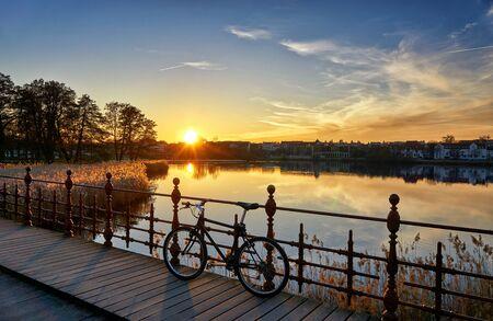 Hermosa puesta de sol en un puente con una bicicleta.