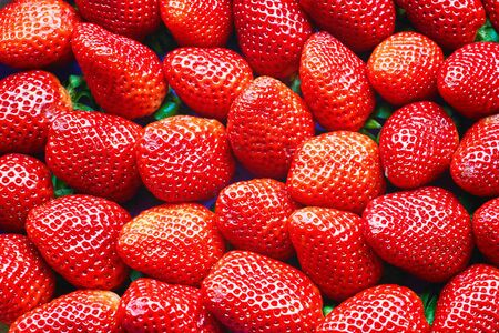 Freshly harvested strawberries directly above as a red background.