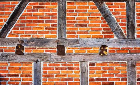 Old half-timbered made wooden with old red bricks as background. Stockfoto