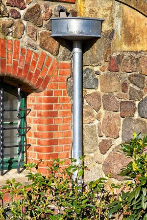 Old antique downpipe at a natural stone wall. 版權商用圖片