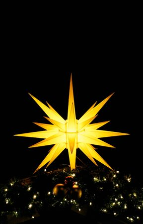 Shiny christmas star as a vertical background. Christmas decoration in the night.