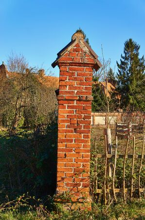Old brick red wall pillars with wooden fence. Stockfoto