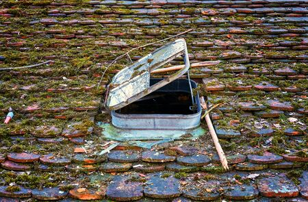 Old window on a roof with rotted roof tiles.