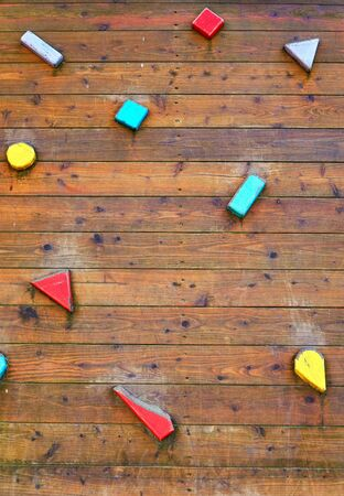 Closeup of wooden climbing wall with colorful handles.