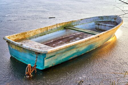 Old rowboat on a frozen lake in winter.