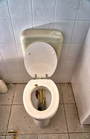 Toilet with feces and urine stained in a dirty bathroom.