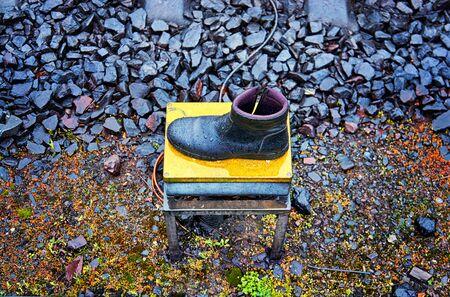 A lost male black shoe near the rails of the railroad.