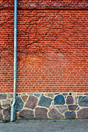Downpipe on a red brick wall with natural stone foundation.