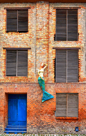 Facade of an old industrial brick house with mermaid, old door and windows. Old town of Stralsund in Germany.